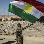 Kurdish peshmerga fighters fly a Kurdish flag in the city of Sinjar, Iraq, Nov. 13, 2015. Deafening bursts of celebratory gunfire erupted after Yazidi fighters helped the Kurds gain control of the city Friday, which has been under the brutal domination of the Islamic State for more than 15 months. (Bryan Denton/The New York Times)