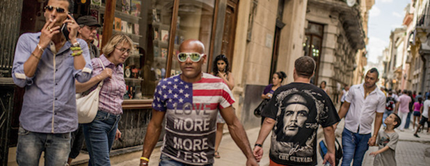 FILE -- A man wears a T-shirt with the American flag as he passes a tourist in a Che Guevara T-shirt in Havana, Dec. 22, 2014. As diplomatic relations between the U.S. and Cuba thaw, an unexpected outburst of American flag waving here has followed. (The New York Times)